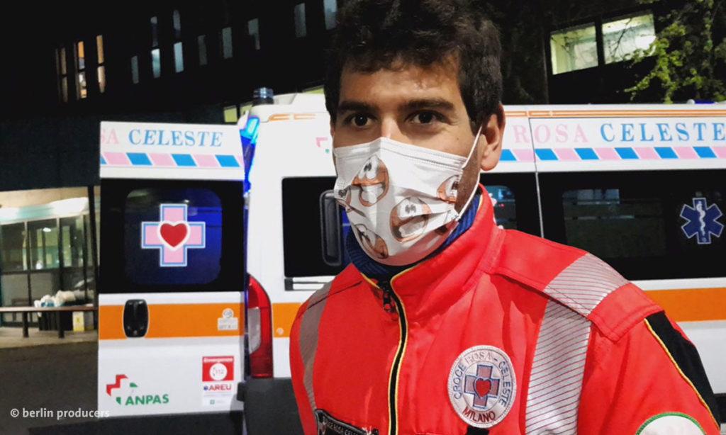 Filmstill aus den Corona Chroniken: Ein Sanitäter vor einem Rettungswagen (© berlin producers)