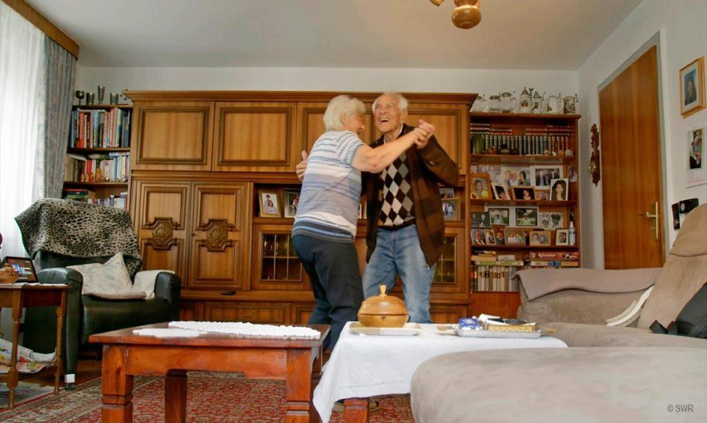 Filmstill: Alexa bitte einen Walzer spielen - älteres Paar tanzt im Wohnzimmer (© SWR)
