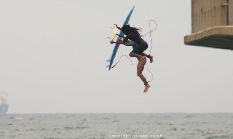 """Filmstill aus """"Chicks on Boards"""": Surferin beim Sprung (© Labo M.)"""